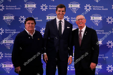 New York Giants NFL football quarterback Eli Manning poses for a photo with former general manager Ernie Accorsi, left, and former coach Tom Coughlin, right, after announing his retirement, in East Rutherford, N.J