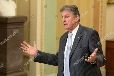 Stock Photo of Sen. Joe Manchin, Joe, D-W.Va., gestures to a staffer as he walks to the Senate chamber for the impeachment trial of President Donald Trump at the U.S. Capitol, in Washington