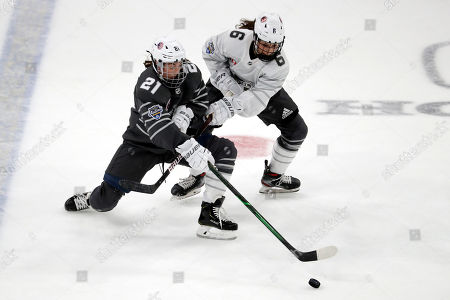 Stock Picture of United States' Hilary Knight (21) and Canada's Rebecca Johnston (6) battle for the puck during the first period in the women's 3-on-3 game, part of the NHL hockey All-Star weekend, in St. Louis