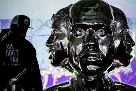 A guest looks at a statue of Kanye West entitled 'North South East West' by US artist David Weeks unveiled at Sneakertopia in Los Angeles, California, USA, 24 January 2020.