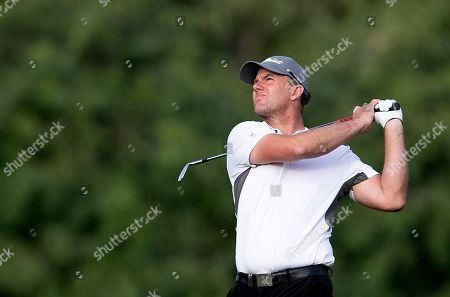 Sweden's Robert Karlsson follows his ball on the 18th hole during the third round of the Dubai Desert Classic golf tournament in Dubai, United Arab Emirates