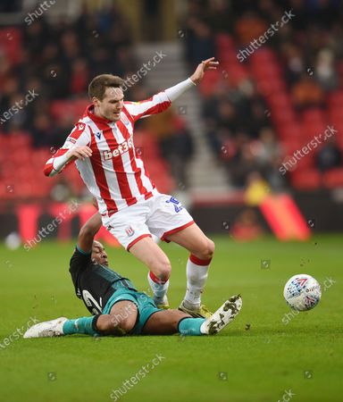 Nick Powell of Stoke City is challenged by Andre Ayew of Swansea City.