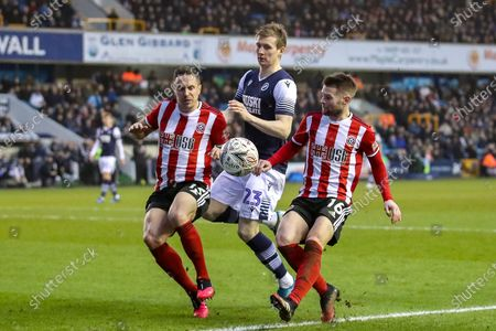 Millwall forward Jón Dadi Bödvarsson (23) held off by Sheffield United defender Phil Jagielka (15) and Sheffield United midfielder Oliver Norwood (16) during The FA Cup match between Millwall and Sheffield United at The Den, London