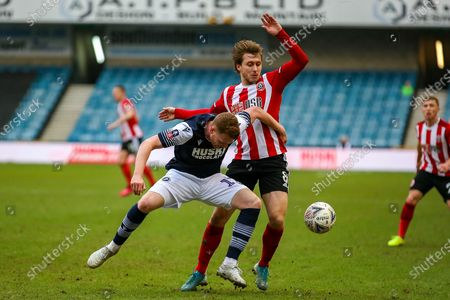 Millwall defender James Brown (17) tussles with Sheffield United midfielder Luke Freeman (8) during The FA Cup match between Millwall and Sheffield United at The Den, London