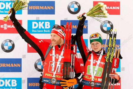 Simon Eder of Austria, left and Lisa Theresa Hauser of Austria celebrate third place at the Single Mixed Relay 6 km / 7,5 km competition at the biathlon World Cup in Pokljuka, Slovenia