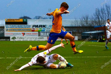 Danny Rose of Mansfield Town hurdles a tackle from Connor Wood of Bradford City