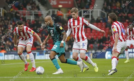 Stock Picture of Andre Ayew of Swansea is caught by Liam Lindsay of Stoke City and Danny Batth of Stoke City