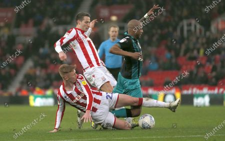 Stock Image of Andre Ayew of Swansea is downed by Sam Clucas of Stoke City