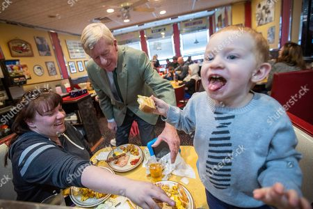 Stock Photo of Bill Weld. Republican presidential candidate and former Massachusetts Gov. William Weld, center, greets Chelsea Guneauat, left, of Derry, N.H. and her son Mason Sylvester while they have breakfast at MaryAnn's Diner, in Derry, N.H