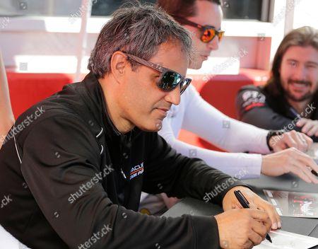Acura Team Penske driver Juan Pablo Montoya signs autographs before the Rolex 24 hour auto race at Daytona International Speedway, in Daytona Beach, Fla