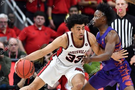 Louisville forward Jordan Nwora (33) attempts to get through the defense of Clemson guard John Newman III (15) during the first half of an NCAA college basketball game in Louisville, Ky