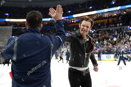Mike Dirnt, right, of the group Green Day, leaves the ice after performing between NHL hockey All Star games, in St. Louis