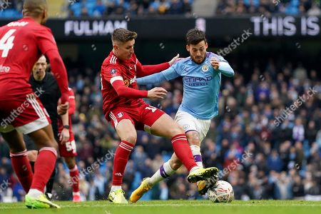 Manchester City's David Silva, right, vies for the ball with Fulham's Tom Cairney during an English FA Cup fourth round soccer match between Manchester City and Fulham at the Etihad Stadium in Manchester, England