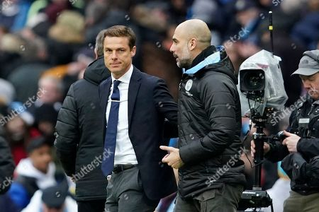 Fulham head coach Scott Parker, left, and Manchester City's head coach Pep Guardiola talk at the end of an English FA Cup fourth round soccer match between Manchester City and Fulham at the Etihad Stadium in Manchester, England