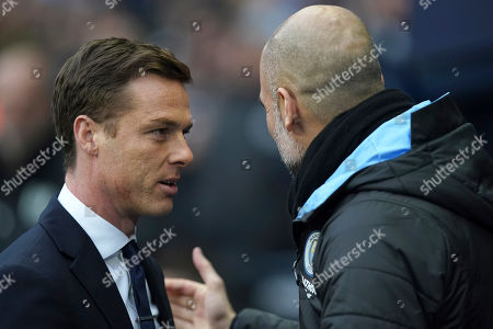 Fulham head coach Scott Parker and Manchester City's head coach Pep Guardiola, right, greet each other before an English FA Cup fourth round soccer match between Manchester City and Fulham at the Etihad Stadium in Manchester, England