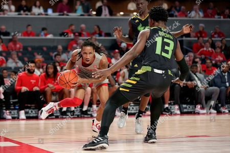 Houston guard Caleb Mills, left, looks to drive around South Florida forward Justin Brown (13) during the second half of an NCAA college basketball game, in Houston