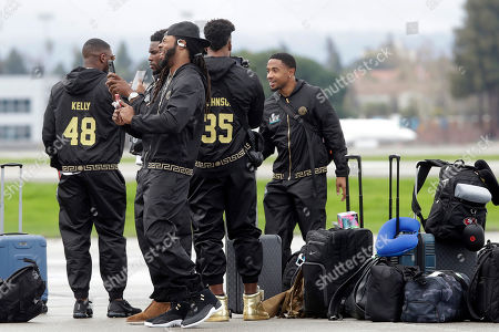 San Francisco 49ers cornerback Richard Sherman, foreground, laughs while taking photos of teammates as they depart from Mineta San Jose International Airport in San Jose, Calif., for Miami, . The 49ers will face the Kansas City Chiefs in Super Bowl 54