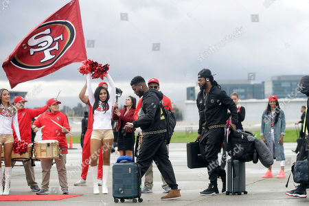San Francisco 49ers free safety Jimmie Ward, center left, and cornerback Richard Sherman board a plane as the team departs from Mineta San Jose International Airport in San Jose, Calif., for Miami, . The 49ers will face the Kansas City Chiefs in Super Bowl 54