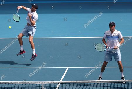 Mike Bryan, right, of the U.S. hits a forehand return as his brother Bob watches during their third round doubles match against Croatia's Ivan Dodig and Slovakia's Filip Polasek at the Australian Open tennis championship in Melbourne, Australia