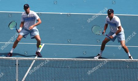 Mike Bryan, left, of the U.S. and his brother Bob play during their third round doubles match against Croatia's Ivan Dodig and Slovakia's Filip Polasek at the Australian Open tennis championship in Melbourne, Australia