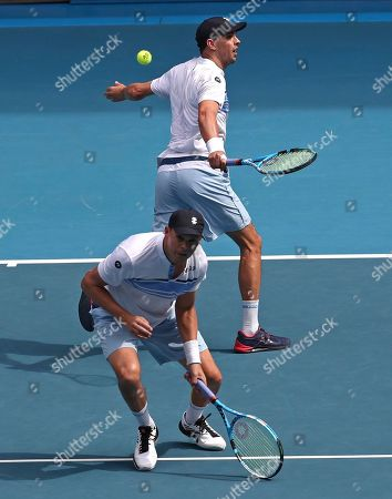 Mike Bryan, top, of the U.S. and his brother Bob play during their third round doubles match against Croatia's Ivan Dodig and Slovakia's Filip Polasek at the Australian Open tennis championship in Melbourne, Australia