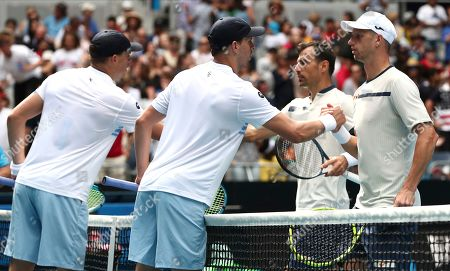 Mike Bryan, second left, of the U.S. and his brother Bob, left, congratulate Croatia's Ivan Dodig and Slovakia's Filip Polasek, right, after winning third round match at the Australian Open tennis championship in Melbourne, Australia