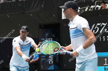 Mike Bryan, left, of the U.S. makes a backhand return as his brother Bob watches during their third round doubles match against Croatia's Ivan Dodig and Slovakia's Filip Polasek at the Australian Open tennis championship in Melbourne, Australia