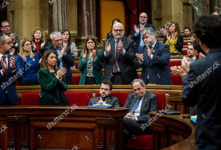 Catalan President Joaquim Torra is applauded by members of his party at the Parliament of Catalonia in Barcelona, Spain,. The Catalan regional parliament is leaving the president of the prosperous and troubled northeastern region without his lawmaker's seat because he disobeyed Spain's strict rules on election propaganda. Monday's move is likely to fuel anger among die-hard pro-independence supporters, who see behind Monday's decision by the electoral board of Catalonia's parliament yet another grievance from Spanish judicial decisions