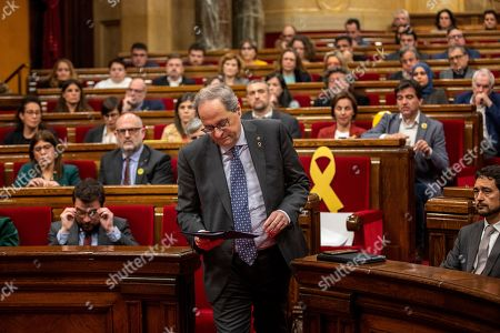 Catalan President Joaquim Torra walks to the stand to deliver a speech at the Parliament of Catalonia in Barcelona, Spain,. The Catalan regional parliament is leaving the president of the prosperous and troubled northeastern region without his lawmaker's seat because he disobeyed Spain's strict rules on election propaganda. Monday's move is likely to fuel anger among die-hard pro-independence supporters, who see behind Monday's decision by the electoral board of Catalonia's parliament yet another grievance from Spanish judicial decisions