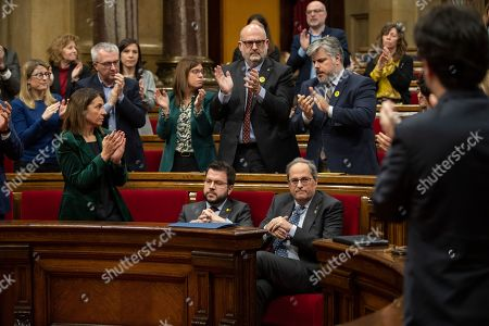 Catalan President Joaquim Torra, right, is applauded by members of the government at the Parliament of Catalonia in Barcelona, Spain,. The Catalan regional parliament is leaving the president of the prosperous and troubled northeastern region without his lawmaker's seat because he disobeyed Spain's strict rules on election propaganda. Monday's move is likely to fuel anger among die-hard pro-independence supporters, who see behind Monday's decision by the electoral board of Catalonia's parliament yet another grievance from Spanish judicial decisions
