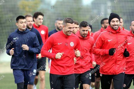 Lukas Podolski, centre, of Germany, smiles as he trains with his new soccer team Antalyaspor in Antalya, Turkey