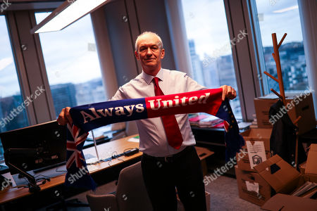 British European Parliament member and leader of Labour Party delegation Richard Corbett shows a scarf to the photographer as he packs some of his belongings at his office at the European Parliament in Brussels, . The U.K. is due to leave the EU on Friday, the first nation in the bloc to do so. It then enters an 11-month transition period in which Britain will continue to follow the bloc's rules while the two sides work out new deals on trade, security and other areas