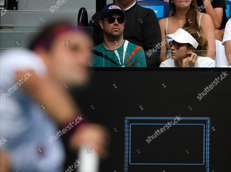 Mirka Federer, right, watches her husband Roger serve during his quarterfinal match against Tennys Sandgren of the U.S. at the Australian Open tennis championship in Melbourne, Australia