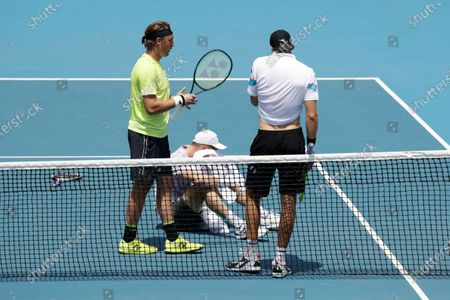 Joe Salisbury (C) of Britain sits on the court after being hit by a tennis ball during his men's doubles round four match with partner Rajeev Ram of USA  against Jan-Lennard Struff (L) of Germany and Henri Kontinen (R) of Finland at the Australian Open Grand Slam tennis tournament in Melbourne, Australia, 28 January 2020.