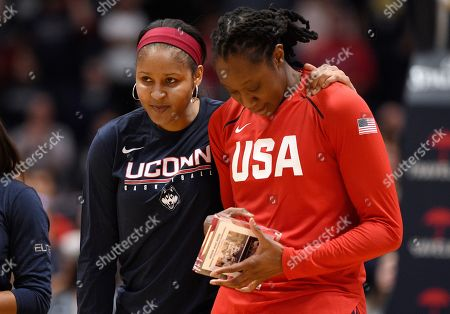 Stock Image of Minnesota Lynx and former Connecticut player Maya Moore, left, puts her arm around former Connecticut teammate and New York Liberty player Tina Charles during a ceremony honoring their championship team before an exhibition basketball game between Connecticut and the United States, in Hartford, Conn