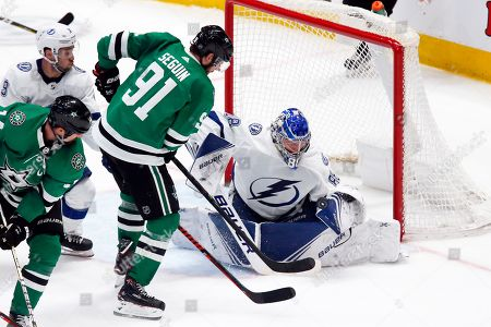 Tampa Bay Lightning goaltender Andrei Vasilevskiy, right, makes the save on Dallas Stars center Tyler Seguin, left, during the second period of an NHL hockey game in Dallas