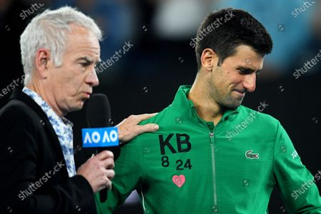 Novak Djokovic (R) of Serbia wears the initials and numbers of late US basketball legend Kobe Bryant on his jacket as he is interviewed by US tennis legend John McEnroe (L) after winning his quarter final match against Milos Raonic of Canada at the Australian Open Grand Slam tennis tournament at Rod Laver Arena in Melbourne, Australia, 28 January 2020.
