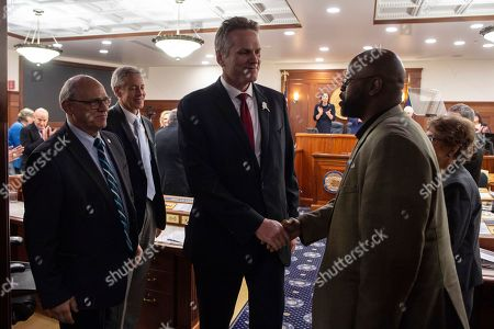 Gov. Mike Dunleavy, center, shakes hands with Sen. David Wilson, right, as he leaves the House chambers after delivering his State of the State speech to a Joint Session of the Alaska Legislature at the Alaska State Capitol in Juneau, Alaska