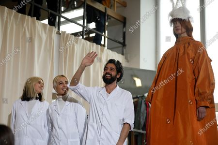Stock Photo of Spanish designer Moises Nieto (C) acknowledges the reaction of spectators of his show as a model (R) presents one of his creations during the Mercedes-Benz Fashion Week Madrid at the University of Fine Arts in Madrid, Spain, 28 January 2020. The Mercedes-Benz Fashion Week Madrid runs from 28 January to 02 February 2020.