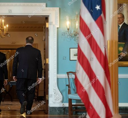 A painting of former Secretary of State Jim Baker is seen at right as Secretary of State Mike Pompeo walks to his office while meeting with Benin President Patrice Talon, at the State Department. in Washington