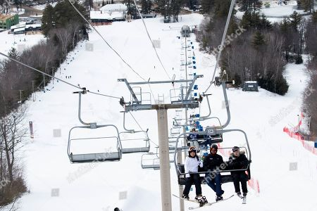 Democratic presidential candidate Rep. Tulsi Gabbard, D-Hawaii, white jacket, rides the ski lift while snowboarding with supporters and staff at Cranmore Mountain Resort, in North Conway, N.H