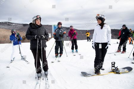 Democratic presidential candidate Rep. Tulsi Gabbard, D-Hawaii, right, talks to supporters and staff after getting off the chairlift while snowboarding at Cranmore Mountain Resort, in North Conway, N.H