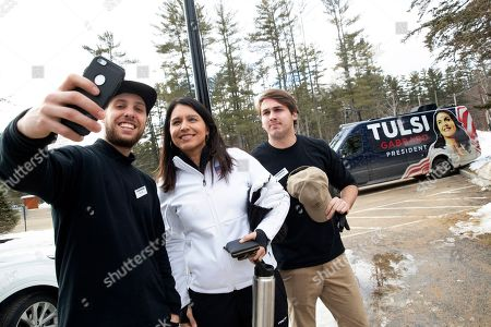 Democratic presidential candidate Rep. Tulsi Gabbard, D-Hawaii, center, takes a selfie with members of the staff at Cranmore Mountain Resort, in North Conway, N.H