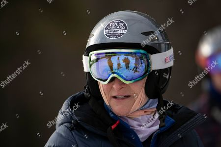 Supporter of Democratic presidential candidate Rep. Tulsi Gabbard, D-Hawaii, Robin Tyner's, looks to the candidate as they snowboard at Cranmore Mountain Resort, in North Conway, N.H. Gabbard, is a white jacket, can be seen in the goggles' reflection