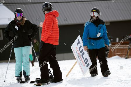 A staff member of Democratic presidential candidate Rep. Tulsi Gabbard, D-Hawaii, carries a Tulsi sign as he arrives to snowboard with her and supporters at Cranmore Mountain Resort, in North Conway, N.H