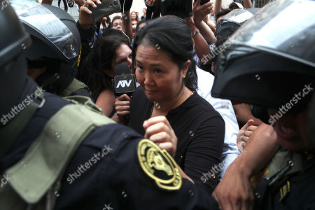 Keiko Fujimori, the daughter of Peru's former President Alberto Fujimori and opposition leader, enters to the courtroom in handcuffs in Lima, Peru, . In a court session a judge decided she must return to preventive detention pending a corruption investigation