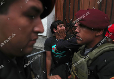 A supporter of Keiko Fujimori, the daughter of Peru's former President Alberto Fujimori and opposition leader, is held back by police officers outside of courtroom in Lima, Peru, . A Peruvian judge ordered 15 months of preventive detention for right-wing politician Keiko Fujimori while she is investigated for alleged money laundering by Brazilian construction company Odebrecht