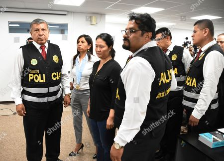 In this handout photo provided by Peru's Palace of Justice Press Office, Keiko Fujimori, the daughter of Peru's former President Alberto Fujimori and opposition leader, center, is escorted by police inside the courtroom in Lima, Peru, . A Peruvian judge ordered 15 months of preventive detention for Keiko Fujimori while she is investigated for alleged money laundering related to the Brazilian construction company Odebrecht