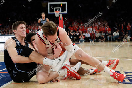Villanova's Collin Gillespi, left, and St. John's David Caraher fight for control of the ball during the first half of an NCAA college basketball game, in New York