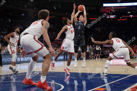 Villanova's Collin Gillespie (2) shoots over St. John's Nick Rutherford (24) during the first half of an NCAA college basketball game, in New York